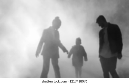 Blurred photo of silhouettes of couple with child in fog. Relations in family abstract background. Black and white photo