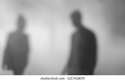 Blurred photo of silhouettes of couple in fog. Relations abstract background. Break up, quarrel concepts. Black and white photo.