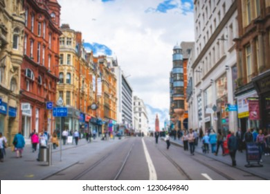Blurred photo Wide view of  beautiful city center street full of random people in a sunny summer day. amazing architecture buildings and shops with blue cloudy sky