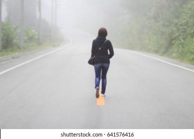 blurred photo Women walk alone on the street.