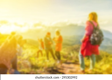 blurred photo of young tourists with backpacks enjoying valley view from top of a mountain on morning sunlight, filtered color.