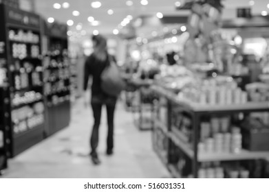 Blurred photo of young woman searching for Christmas gifts in the store. Black and white.