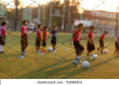 Blurred photo of youth training football in the football practice field. Sport concept.