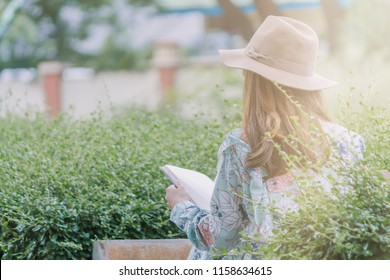 blurred photo,A young girl in a vintage floral dress wore a brown wide-haired hat reading the Bible inside the park alone in the morning to study God's teachings and pray at the same time.