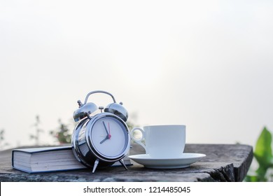 blurred photo,The alarm clock that was set in the morning was placed on the terrace so that the alarm clock wakes the man to eat coffee and read the book in the morning on a beautiful sunbeam.