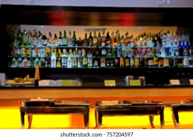 Blurred picture of alcohol drink on bar counter in the dark night background, blur of bottles counter bar Background, blurred image of liquor shop and wine on the shelves on counter bar