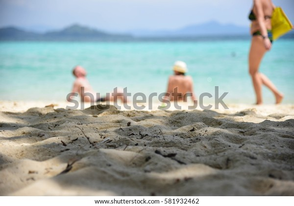 Blurred picture of a beach unrecognizable people sunbathing.