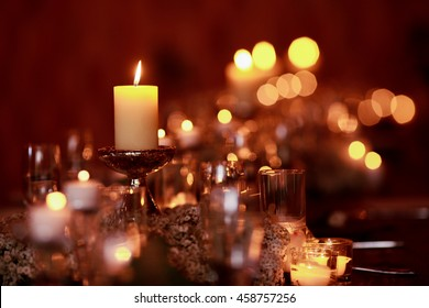 A blurred picture of candles burning on the dinner table