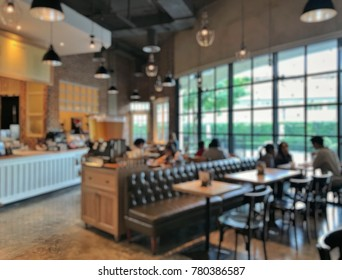 Blurred picture of coffee shop with customers in a cozy atmosphere; Blurred picture of Relaxing atmosphere of a cafe with large framed windows and warm light; Meetings place for relaxing after work.