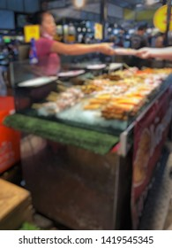 Blurred picture of customer hand send the money to merchant in the night scene at the street food market