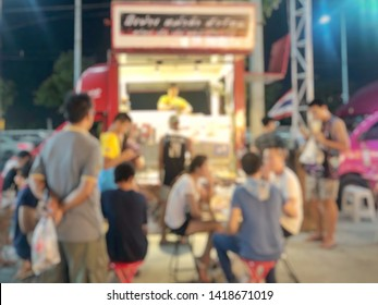 Blurred picture of customer waiting for order of food truck in the night scene at the street food market