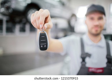 Blurred picture of key that worker hold in hand. He look at it and smile a bit. Young man stand in garage. There is car on platform behind him.