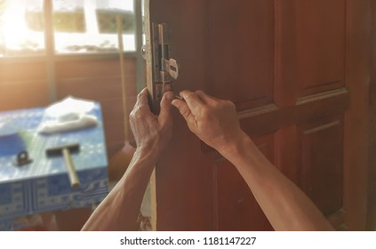 Blurred picture of middle-aged men, to repair the latches, wooden house.