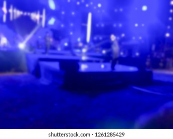 Blurred picture of music band perform on a concert stage with color light shining. Singer hold microphone and walk on stage.