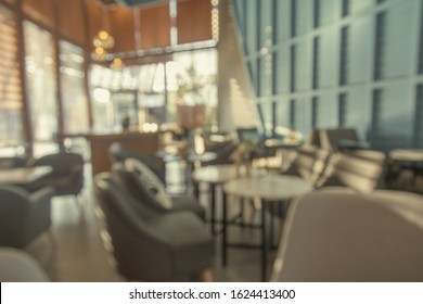 Blurred picture of relaxing seats or sofa in pastel modern coffee shop (café restaurant, co-working space). Use for modern-style concept.