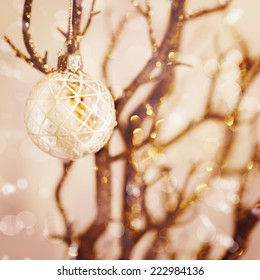 Blurred picture of white snowy Christmas decoration with baubles on the branch. Nice bokeh lights, instagram vintage effect.