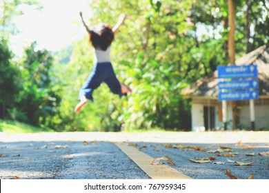 Blurred picture of woman jumping in the air while walking on the way, girl jumping on road while relaxing time in happy and freedom day, happy young female tourist jumping on the road on travel trip