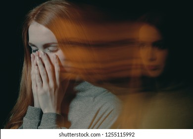 Blurred picture of young beautiful redhead girl with obsessive compulsive disorder covering her mouth and closing her eyes