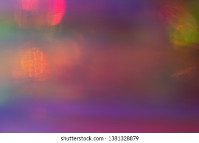 Blurred pink and purple abstract lens flare background. Defocused glow effect. Illuminated bokeh