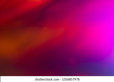 Blurred pink and red abstract lens flare background. Defocused glow effect. Illuminated bokeh