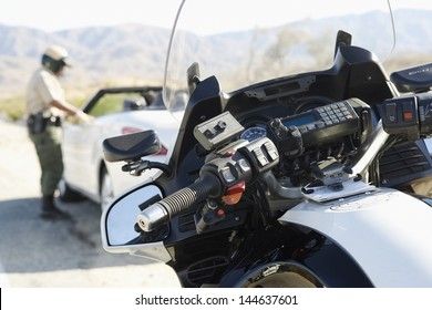 Blurred police officer talking to driver of stopped car on desert highway with focus on motorbike