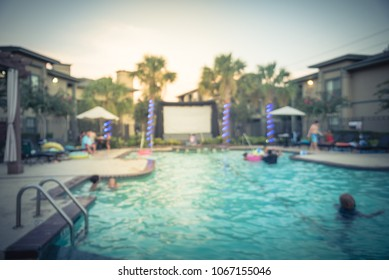 Blurred pool party at apartment complex in America. Family oriented event with kids swimming and huge inflatable outdoor projector for open air cinema