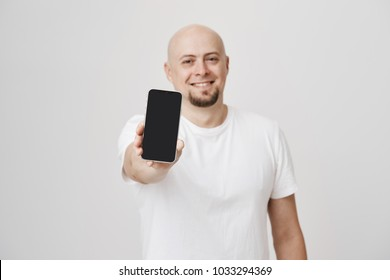 Blurred portrait of attractive bald adult caucasian male extending hand with smartphone towards camera, smiling broadly and standing over gray background. Store owner shows new arrival
