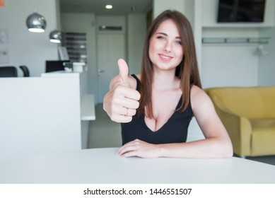 Blurred Portrait of happy smiling young woman with deep decollete and focused thumb up hand sitting behind the desk in the office hall. Selective focus, copy space