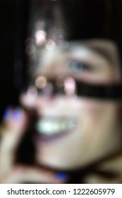 A blurred portrait of a laughing, and black masked sadomasochism woman.