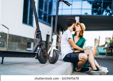 Blurred portrait of man and woman sitting and kissing near a modern glass building. with their electric scooters. In the foreground are their electric scooters.