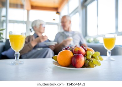 Blurred portrait of modern senior couple enjoying breakfast in cafe, focus on fruit bowl and two glasses of orange juice on table in foreground