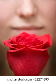 blurred portrait of woman is smelling red flower rose