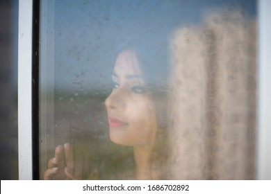 Blurred portrait of an young Indian brunette woman in red dress looking outside through a glass window with water droplets/dewdrops in home quarantine. Indian lifestyle and quarantine.