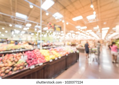 Blurred produce section at modern grocery store in America. Customers choosing, picking up fresh and organic vegetables, fruits. Healthy diet abstract background.