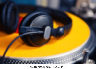 Blurred professional DJ headphones laying on yellow clipmat on turntable vinyl records player.Turntables platter in focus,no record.Pro analog audio equipment
