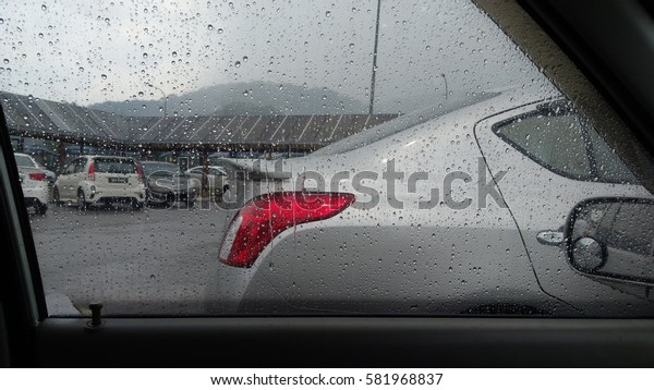Blurred rain drop on the car glass background, water drops at the car window driver side, vintage color