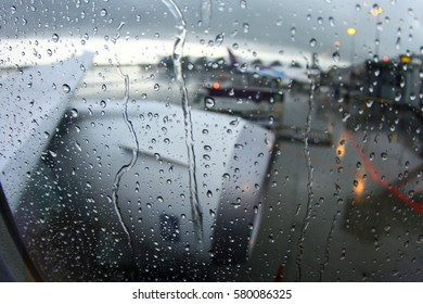 Blurred rain drops on aircraft window, passenger's view from inside of an airplane, water spray on window surface of an aircraft, cloudy day at the airport