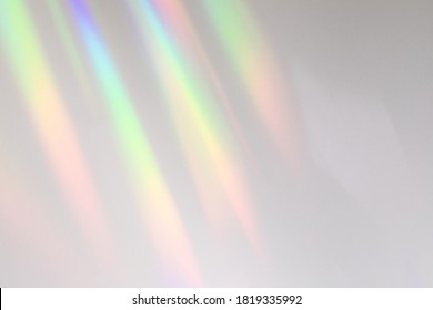 Blurred rainbow light refraction texture overlay effect for photo and mockups. Organic drop diagonal holographic flare on a white wall. Shadows for natural light effects