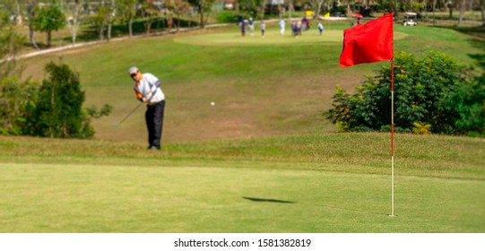 Blurred red flag on blurred golfer hitting ball to fairway in golf course on hills