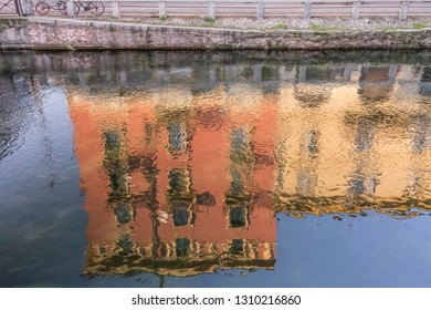blurred reflection of old facades in Naviglio canal water,  shot in bright winter light at Milan, Lombardy,  Italy
