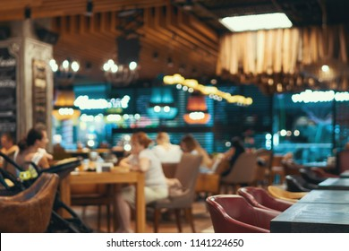 Blurred restaurant or cafe background. Tables and chairs. Visitors to the family restaurant for dinner. Beautiful bright interior. Blurred background bokeh background for design