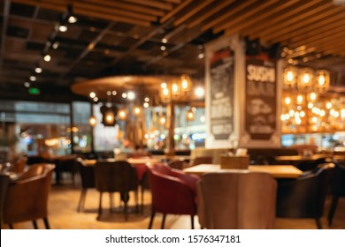 Blurred restaurant or cafe background. Tables and chairs in the lobby of restaurant. Visitors to restaurant for dinner. Cozy bokeh lightening. Beautiful bright interior. Blurred bokeh basic background
