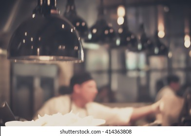 Blurred Restaurant Chef: Chef cooking in the open kitchen, customer can see cooking at food counter