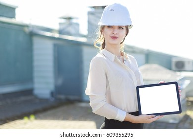 Blurred roof on background, attractive brunette caucasian business lady in white blouse, watch, white helmet and black skirt stand on the roof and show empty tablet, look left