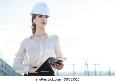 Blurred roof on background, pretty brunette caucasian business lady in white blouse, watch, white helmet and black skirt stand on the roof and hold tablet, thinking