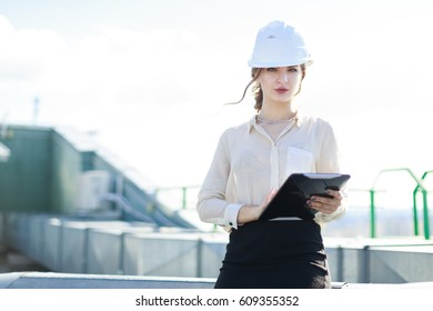 Blurred roof on background, pretty brunette caucasian business lady in white blouse, watch, white helmet and black skirt stand on the roof and hold tablet, look at camera