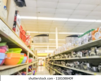 Blurred round plastic basket, bucket and stainless steel frying pan, pot. Wide selection of houseware, kitchenware on shelves at Asian supermarket in USA. Kitchen hand-held tools, gadget necessities
