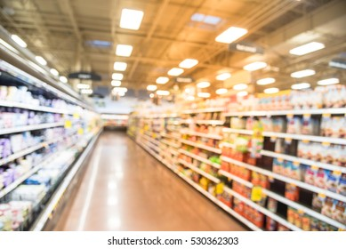 Blurred row of fridge shelves with different brands and flavors of yogurt at local store in Humble, Texas, US.  Variety of yogurt and frozen foods in refrigerator aisle, defocused bokeh light.