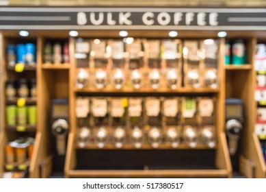 Blurred row of variety organic raw coffee beans in vending machine at grocery store in Houston, Texas, US. Bulk coffee sell container, stainless copper, grinder to grind whole beans before brewing