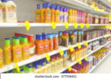 Blurred salad dressing selection at a supermarket